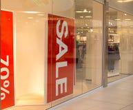 Σημάδια πώλησης στην προθήκη στο κατάστημα μόδας στη λεωφόρο αγορών στοκ εικόνα