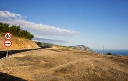 Σημάδια στη στροφή του δρόμου στα βουνά πέρα από τη θάλασσα στοκ εικόνες με δικαίωμα ελεύθερης χρήσης