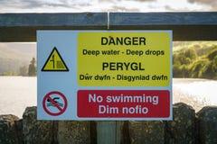 Σημάδι: Βαθιές πτώσεις βαθιά νερών κινδύνου τα κανένα κολυμπώντας ουαλλικά & αγγλικά Στοκ Εικόνα