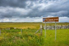 Σημάδι για το μαύρο σπίτι Arnol στο γαελικό με το όμορφο σκωτσέζικο τοπίο στο υπόβαθρο στοκ εικόνες