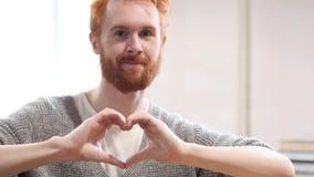 Σημάδι καρδιών από το άτομο με τις κόκκινες τρίχες Στοκ Φωτογραφίες