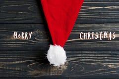 Σημάδι κειμένων Χαρούμενα Χριστούγεννας στο καπέλο santa Χριστουγέννων στο μοντέρνο bla Στοκ εικόνα με δικαίωμα ελεύθερης χρήσης