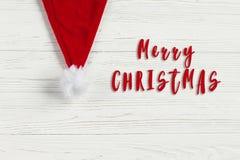 Σημάδι κειμένων Χαρούμενα Χριστούγεννας στο κόκκινο καπέλο santa στο άσπρο αγροτικό woode Στοκ Φωτογραφία