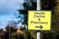Σημάδι κεντρικών κατευθυντικό δρόμων υγείας Farmacy στο δρόμο στο UK στοκ εικόνα