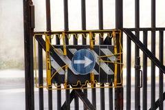Σημάδι κυκλοφορίας σημάδι μονόδρομων με τον προστατευτικούς φράκτη ασφαλείας/το φράκτη μετάλλων με το μπλε βελών σημαδιών κυκλοφο Στοκ Εικόνες