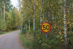 Σημάδι κυκλοφορίας ορίου ταχύτητας από έναν δρόμο αμμοχάλικου Στοκ εικόνες με δικαίωμα ελεύθερης χρήσης