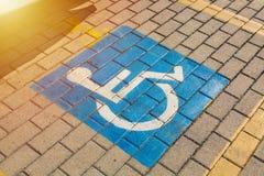 Σημάδι λογότυπων για τα άτομα με ειδικές ανάγκες στο χώρο στάθμευσης στο δρόμο Στοκ Φωτογραφίες