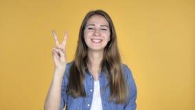 Σημάδι νίκης από την όμορφη γυναίκα που απομονώνεται στο κίτρινο υπόβαθρο απόθεμα βίντεο