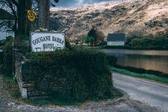 Σημάδι ξενοδοχείων Barra Gougane με το παρεκκλησι ρητορικής Αγίου Finbarr ` s και η λίμνη στο υπόβαθρο στοκ εικόνα