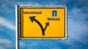 Σημάδι οδών διεθνής εναντίον εθνικός στοκ εικόνες με δικαίωμα ελεύθερης χρήσης