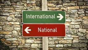 Σημάδι οδών διεθνής εναντίον εθνικός στοκ εικόνα με δικαίωμα ελεύθερης χρήσης