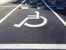 Σημάδι αναπηρίας αναπηρικών καρεκλών στο χώρο στάθμευσης Στοκ Εικόνα