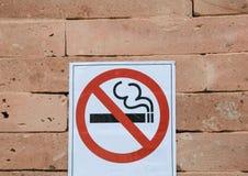 Σημάδι απαγόρευσης του καπνίσματος στον πορτοκαλή τουβλότοιχο στοκ εικόνες
