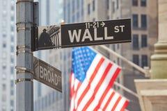 Σημάδι Γουώλ Στρητ κοντά στο χρηματιστήριο με τις αμερικανικές σημαίες Στοκ Εικόνες