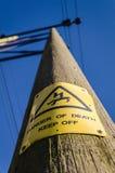Σημάδι ηλεκτροπληξίας προειδοποίησης ενάντια στο μπλε ουρανό στοκ εικόνες
