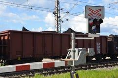 Σημάδι και κόκκινα φώτα στάσεων στο πέρασμα σιδηροδρόμων με τη διάβαση του τραίνου φορτίου Στοκ Εικόνα