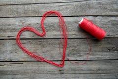 Σημάδι καρδιών που γίνεται από το κόκκινο νήμα Στοκ Φωτογραφία