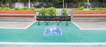 Σημάδι πάρκων ποδηλάτων στη συγκεκριμένη πάροδο με τις θέσεις συνεδρίασης Στοκ εικόνα με δικαίωμα ελεύθερης χρήσης