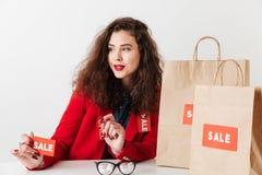 Σημάδι πώλησης εκμετάλλευσης γυναικών αγορών καθμένος με τις τσάντες αγορών Στοκ Εικόνα