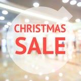 Σημάδι πώλησης εποχής Χριστουγέννων πέρα από το θολωμένο υπόβαθρο Στοκ Φωτογραφίες