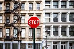 Σημάδι στάσεων μπροστά από τα παλαιά κτήρια στην πόλη της Νέας Υόρκης Στοκ Εικόνες