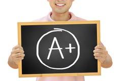 A+ σημάδι στον πίνακα που κατέχει το χαμογελώντας άτομο στοκ φωτογραφία