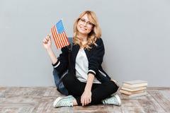 Σημαία εκμετάλλευσης γυναικών σπουδαστών της αμερικανικής συνεδρίασης στο πάτωμα Στοκ εικόνα με δικαίωμα ελεύθερης χρήσης