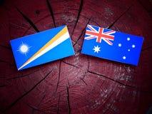 Σημαία Νησιών Μάρσαλ με την αυστραλιανή σημαία σε ένα κολόβωμα δέντρων που απομονώνεται Στοκ φωτογραφία με δικαίωμα ελεύθερης χρήσης