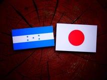 Σημαία Ονδουριανών με την ιαπωνική σημαία σε ένα κολόβωμα δέντρων που απομονώνεται Στοκ φωτογραφία με δικαίωμα ελεύθερης χρήσης