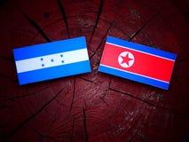 Σημαία Ονδουριανών με τη βόρεια κορεατική σημαία σε ένα κολόβωμα δέντρων Στοκ φωτογραφίες με δικαίωμα ελεύθερης χρήσης