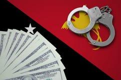 Σημαία Παπούα Νέα Γουϊνέα με τις χειροπέδες και μια δέσμη των δολαρίων Η έννοια των παράνομων τραπεζικών διαδικασιών στο αμερικαν στοκ εικόνα με δικαίωμα ελεύθερης χρήσης