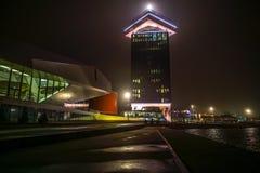 Σημαία πόλεων του Άμστερνταμ στην οικοδόμηση κτηρίου ενάντια στον όμορφο ομιχλώδη ουρανό νύχτας Στοκ φωτογραφία με δικαίωμα ελεύθερης χρήσης