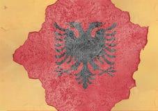Σημαία της Αλβανίας στη μεγάλη συγκεκριμένη ραγισμένη τρύπα και το σπασμένο υλικό Στοκ Φωτογραφία