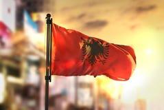 Σημαία της Αλβανίας θολωμένο στο πόλη κλίμα στην ανατολή Backligh Στοκ Εικόνα