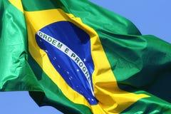 Σημαία της Βραζιλίας ενάντια στους μπλε ουρανούς Στοκ Εικόνα