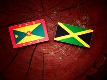 Σημαία της Γρενάδας με την τζαμαϊκανή σημαία σε ένα κολόβωμα δέντρων Στοκ φωτογραφία με δικαίωμα ελεύθερης χρήσης