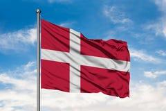 Σημαία της Δανίας που κυματίζει στον αέρα ενάντια στον άσπρο νεφελώδη μπλε ουρανό Δανική σημαία στοκ φωτογραφίες