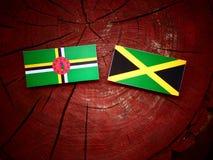 Σημαία της Δομίνικας με την τζαμαϊκανή σημαία σε ένα κολόβωμα δέντρων Στοκ εικόνα με δικαίωμα ελεύθερης χρήσης