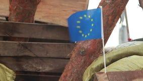 Σημαία της ΕΕ στο ξύλινο οδόφραγμα, διαμαρτυρόμενοι μακριοί για το ευρωπαϊκό μέλλον απόθεμα βίντεο