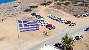 Σημαία της Ελλάδας που κυματίζει στον αέρα, εναέριο πανόραμα ακτών της Κρήτης απόθεμα βίντεο