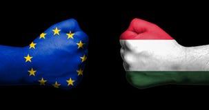 Σημαία της Ευρωπαϊκής Ένωσης και της Ουγγαρίας που χρωματίζονται σε δύο σφιγγμένες πυγμές στοκ εικόνες