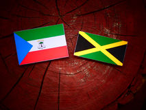 Σημαία της Ισημερινής Γουινέας με την τζαμαϊκανή σημαία σε ένα κολόβωμα δέντρων isolat Στοκ Φωτογραφία