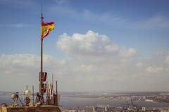 Σημαία της Ισπανίας σε έναν πύργο του φρουρίου Santa Barbara στην Αλικάντε Στοκ Εικόνες