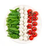 Σημαία της Ιταλίας από τα συστατικά για τη χορτοφάγο υγιή σαλάτα - ντομάτα κερασιών, τυρί μοτσαρελών και arugula σε ένα άσπρο πιά Στοκ Φωτογραφίες