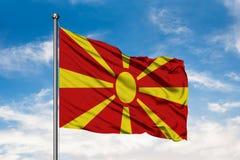Σημαία της Μακεδονίας που κυματίζει στον αέρα ενάντια στον άσπρο νεφελώδη μπλε ουρανό Μακεδονική σημαία στοκ φωτογραφίες