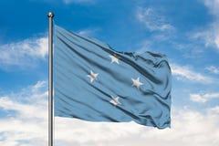 Σημαία της Μικρονησίας που κυματίζει στον αέρα ενάντια στον άσπρο νεφελώδη μπλε ουρανό Συνενωμένα σε ομοσπονδία κράτη της σημαίας στοκ φωτογραφία