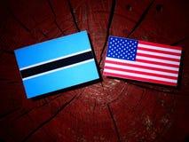 Σημαία της Μποτσουάνα με την ΑΜΕΡΙΚΑΝΙΚΗ σημαία σε ένα κολόβωμα δέντρων Στοκ φωτογραφία με δικαίωμα ελεύθερης χρήσης