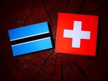 Σημαία της Μποτσουάνα με την ελβετική σημαία σε ένα κολόβωμα δέντρων που απομονώνεται Στοκ εικόνα με δικαίωμα ελεύθερης χρήσης