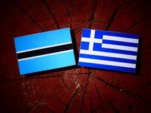 Σημαία της Μποτσουάνα με την ελληνική σημαία σε ένα κολόβωμα δέντρων που απομονώνεται Στοκ Εικόνα