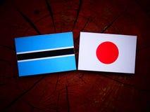 Σημαία της Μποτσουάνα με την ιαπωνική σημαία σε ένα κολόβωμα δέντρων που απομονώνεται Στοκ Εικόνα